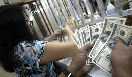 A Filipino trader counts US dollars inside a local money change in Manila